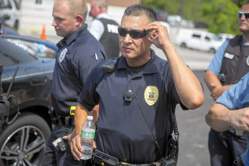 A police officer wears a body camera at a rally for Michael Brown in Ferguson, Mo. Brown, an unarmed black man, was shot and killed by Ferguson police in August. The department began equipping officers with body cameras after the shooting.