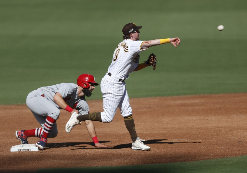 Jake Cronenworth of the San Diego Padres tries to turn a double play in the third inning as Matt Carpenter slides
