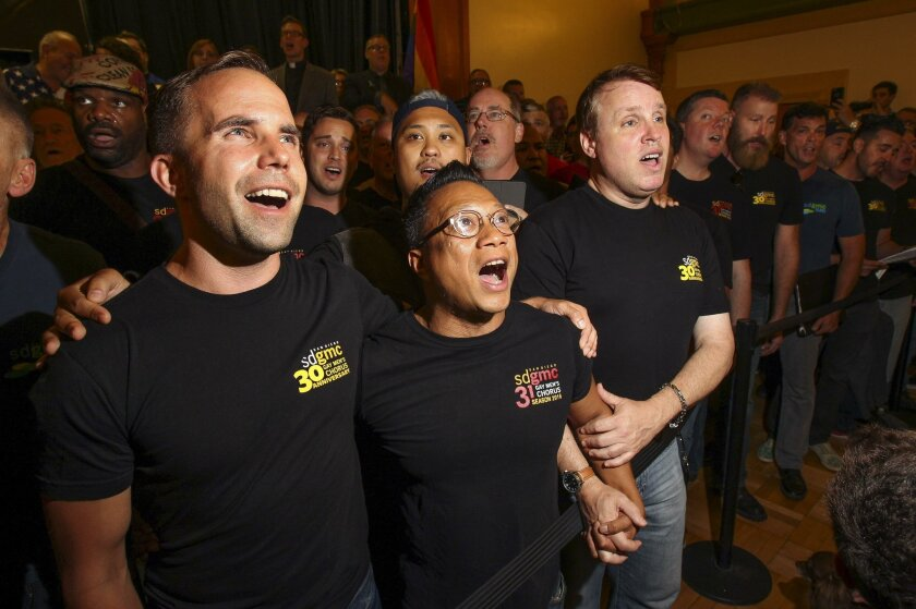 """Members of the San Diego Gay Men's Chorus, from left, Jeremy Bauer, Joe Gregore, and Erik Swanson, sing """"Over The Rainbow"""" with the rest of the chorus members at the San Diego LBGT Community Center as people gather there to show solidarity for the Orlando mass shooting victims."""
