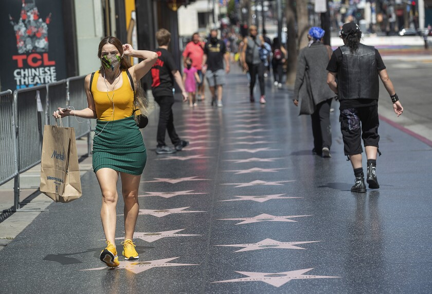 A pedestrian adjusts her face covering while walking along Hollywood Boulevard in Hollywood.