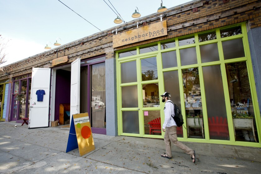 A pedestrian walks by a colorful series of stores, including the Neighborhood Salon and Yogala, along Echo Park Avenue.