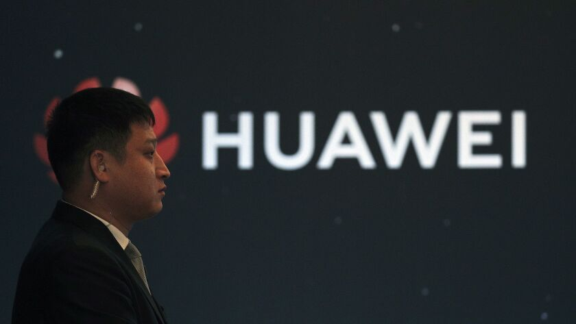 In this Jan. 9, 2019, photo, a security guard stands near the Huawei company logo during a new produ