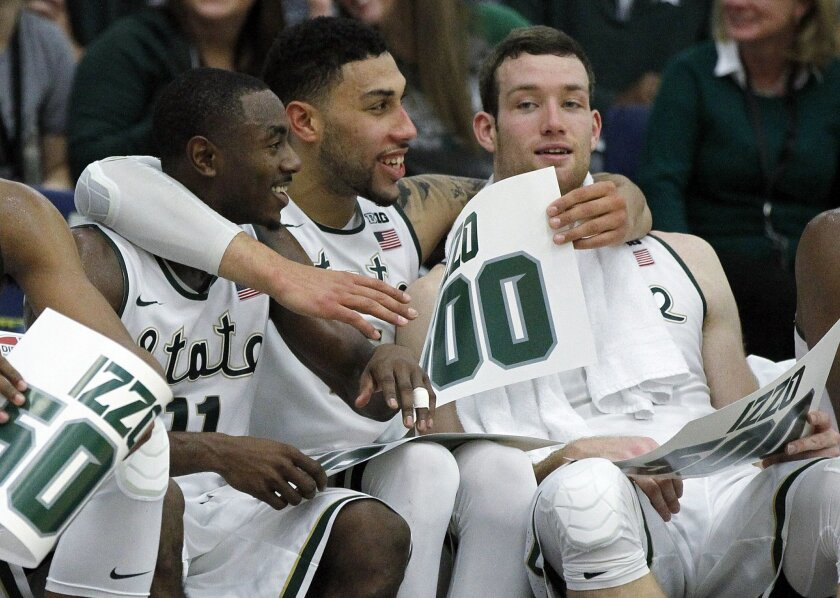 Michigan State guard Lourawls Nairn Jr., left, guard Denzel Valentine, center, and forward Matt Costello celebrate coach Tom Izzo's impending 500th career winm during the second half of an NCAA college basketball game against Boston College in the quarterfinals of the Wooden Legacy tournament in Fullerton, Calif., Thursday, Nov. 26, 2015. Michigan State won 99-68. (AP Photo/Alex Gallardo)