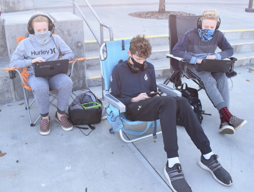 Jacob, Danny and Brandon Sawyer participated in virtual classes while sitting in front of Del Norte High last Thursday.