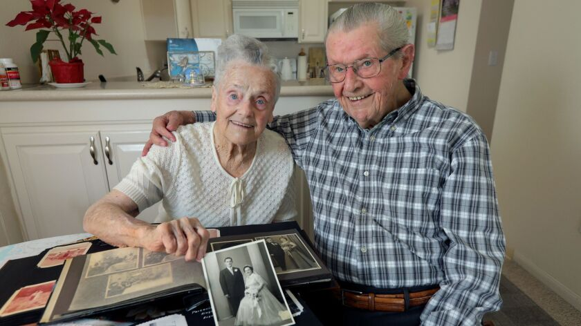 Portrait of Willi and Margarete Kleemeier at their home in the Redwood Terrace retirement community. Margarete is holding their wedding photo taken on September 2, 1955, in Herford, Germany.