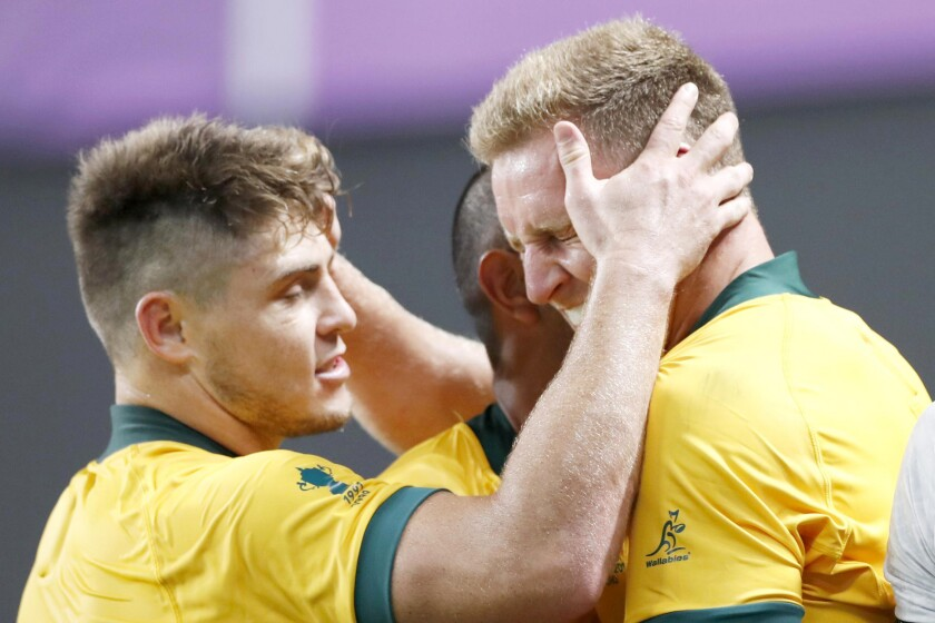 Australia's Reece Hodge, right, is congratulated by teammates after scoring a try during the Rugby World Cup Pool D game at Sapporo Dome between Australia and Fiji in Sapporo, northern Japan, Saturday, Sept. 21, 2019. (Naoya Osato/Kyodo News via AP)