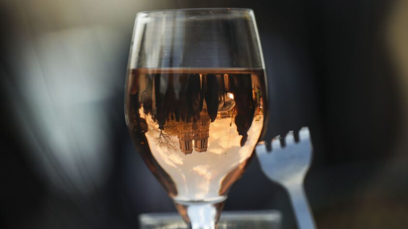 The Notre Dame Cathedral is reflected in a wine glass as a customer eats nearby the cathedral in Par