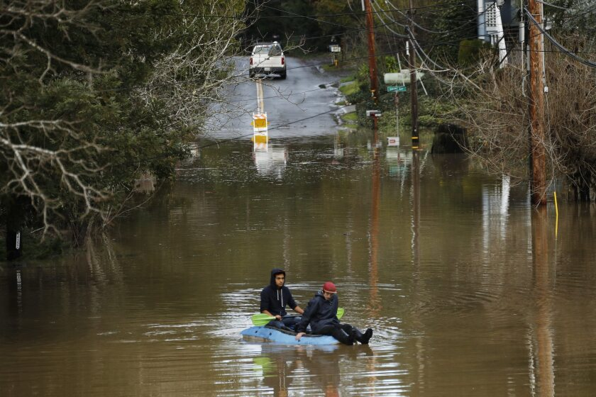 FLOOD WATCH: Residents paddle along River Lands Road in Guerneville.