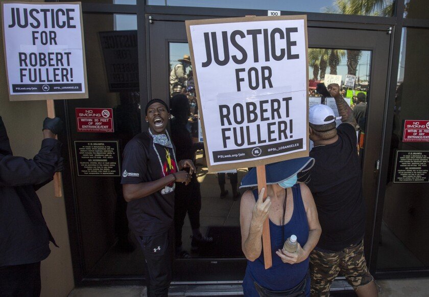 Demonstrators outside a sheriff's station hold signs demanding an investigation into the death of Robert Fuller