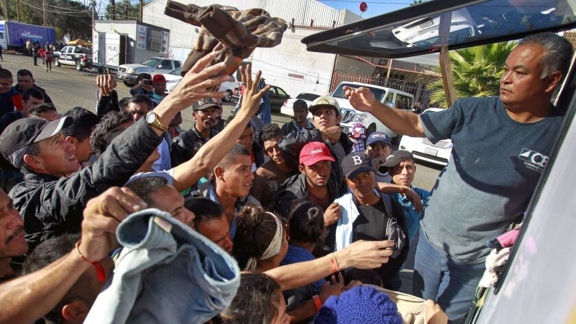 TIJUANA, November 17, 2018 | Pastor Ariosco Vazquez tosses out clothes to the outstretched hands as