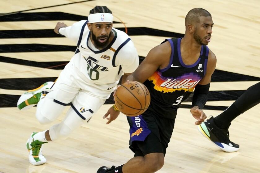 El jugador de los Suns de Phoenix Chris Paul (3) avanza seguido por el jugador del Jazz de Utah Mike Conley (10) en la primera mtiad de su juego de NBA, el miércoles 7 de abril de 2021 en Phoenix. (AP Foto/Matt York)