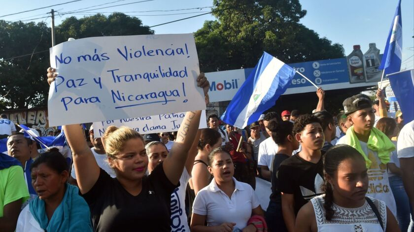 "A demonstrator holds a placard reading ""No More Violence! Peace and Tranquility for Nicaragua!"" during a march on April 23, 2018, demanding that Nicaraguan President Daniel Ortega and his wife, Vice President Rosario Murillo, step down."