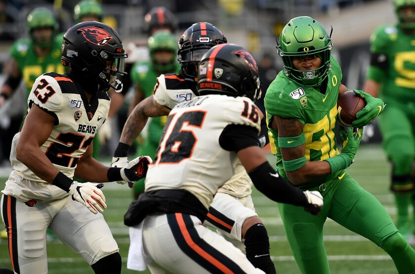 Oregon wide receiver Bryan Addison (80) runs with a pass reception as Oregon State defensive back Isaiah Dunn (23) and defensive back Akili Arnold (16) close in during the second half on Saturday.