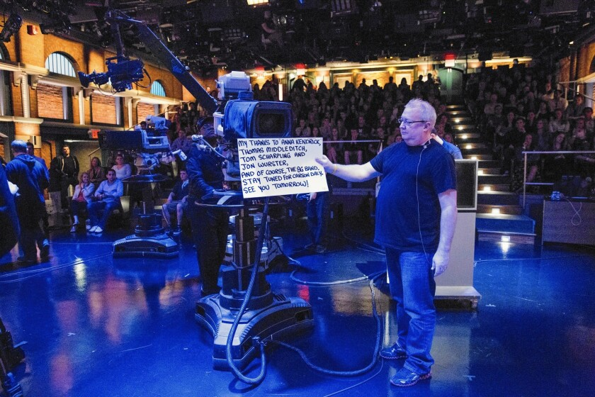 """Wally Feresten holds a cue card on """"Late Night With Seth Meyers"""" on May 14, 2015."""