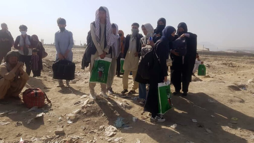 Members of the Afghanistan national girls' youth soccer team and their families are standing and holding bags