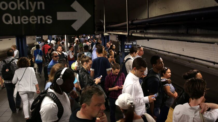 Passengers wait for the A train, the line that was most affected by the recent derailment.