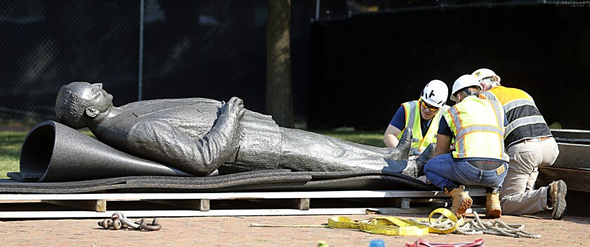 Workers secure the statue of Harry F. Byrd, Sr., former Virginia Governor and U. S. Senator, to a pallett after it was removed from the pedestal in Capitol Square in Richmond, Va. Wednesday, July 7, 2021. The General Assembly approved the removal during the last session. (Bob Brown/Richmond Times-Dispatch via AP)