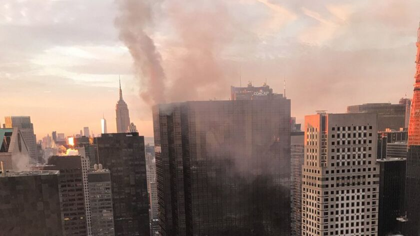 Smoke rises from Trump Tower in New York on Monday. The Fire Department said the fire started around 7 a.m. in the heating and air conditioning system of the building.