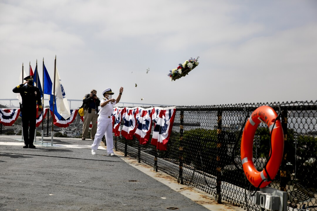 Navy Rear Admiral Bette Bolivar throws a wreath from the deck during a Memorial Day service aboard the USS Midway Museum on May 25, 2020 in San Diego, California.