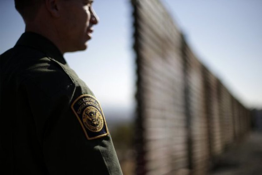 U.S. Border Patrol agent Jerry Conlin looks to the north near where the border wall ends as it separates Tijuana, Mexico, left, and San Diego, right.