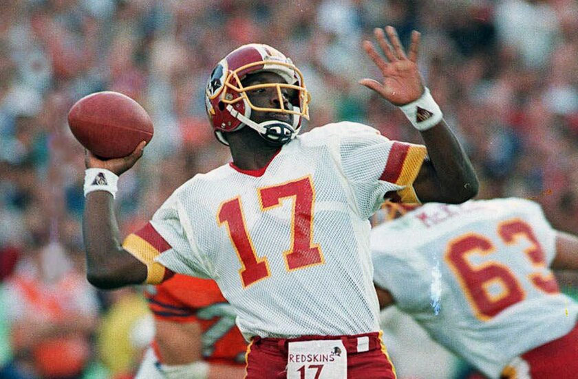 Washington Redskins quarterback Doug Williams prepares to let go of a pass during first quarter of Super Bowl XXII against the Denver Broncos in San Diego. Williams, who set a record with 340 yards passing in the NFL football game and became the first African-American quarterback to win a Super Bow