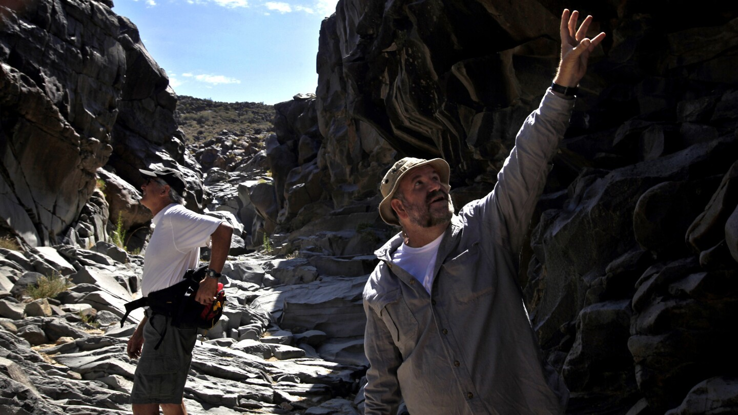 Michael Baskerville, 51, right, explores Little Petroglyph Canyon Paul Goldsmith, who did a documentary on the petroglyphs.