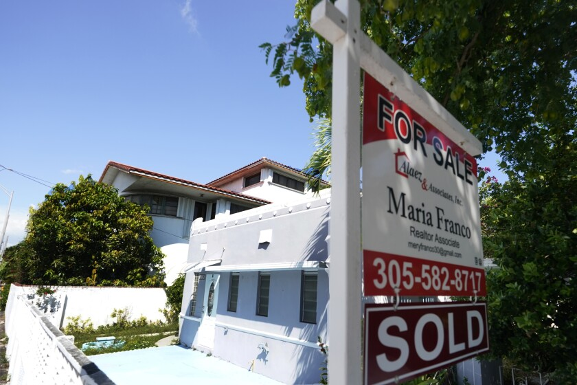 """FILE - In this Oct. 12, 2020 file photo, a home for sale with a """"Sold"""" sign attached is viewed in Miami Beach, Fla. On Thursday, Feb. 11, 2021, U.S. long-term mortgage rates were flat this week for a second straight week. Home-loan rates stayed near record lows as the economy, especially in the services sector, remains burdened by the coronavirus pandemic. (AP Photo/Wilfredo Lee, File)"""