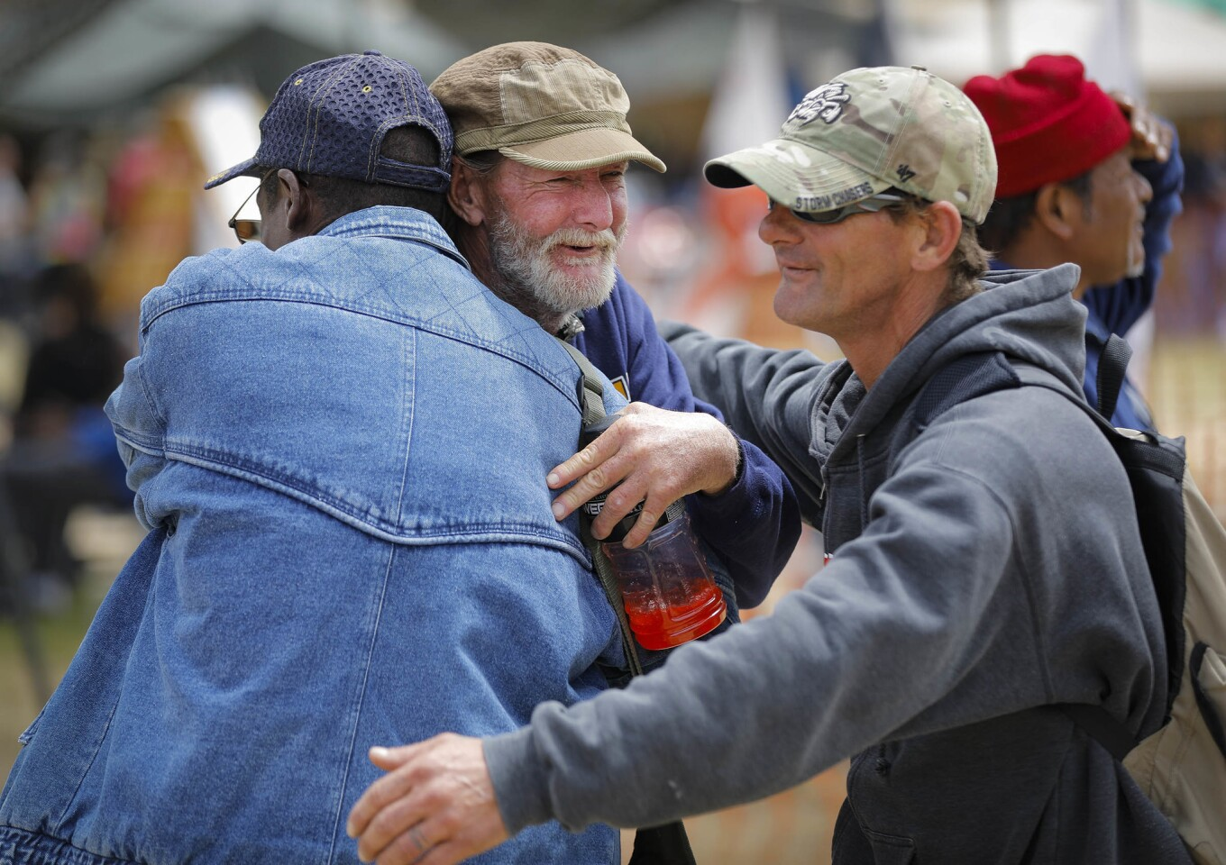 Navy veteran Sean Reilly, center, who has been homeless off and on over the past 15-years gets a hug from from friends during Stand Down 2018 at San Diego High School. The annual three-day event hosted by Veterans Village of San Diego began Friday and will help 800 veterans and their family members with a wide variety of services.