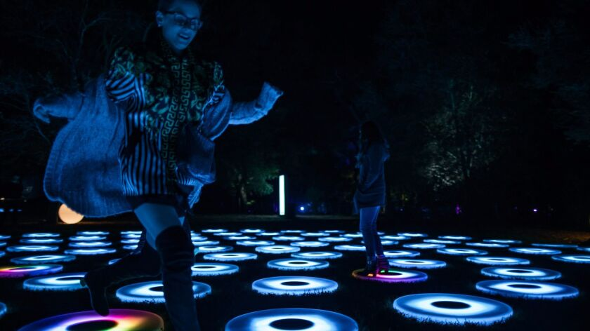 Children stomp and play in an interactive display at Descanso Gardens. As they step, the lights shift colors.The light show runs through Jan. 8.