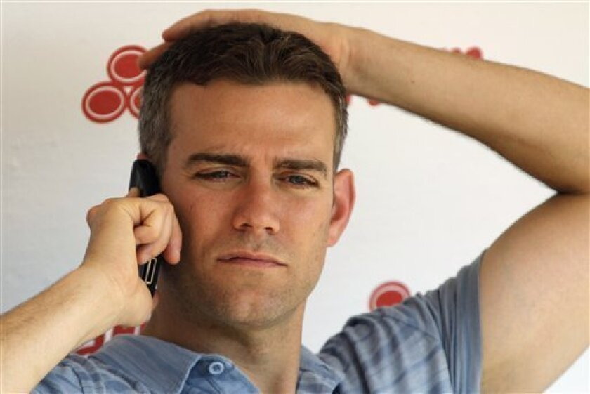 FILE - In this June 15, 2012 file photo, Chicago Cubs President Theo Epstein talks on his phone before an interleague baseball game against the Boston Red Sox in Chicago. Kathleen Kearney, 44, of Canton, Mass., appeared in a Cook County courtroom, Tuesday, July 17, in Chicago, where she was charged