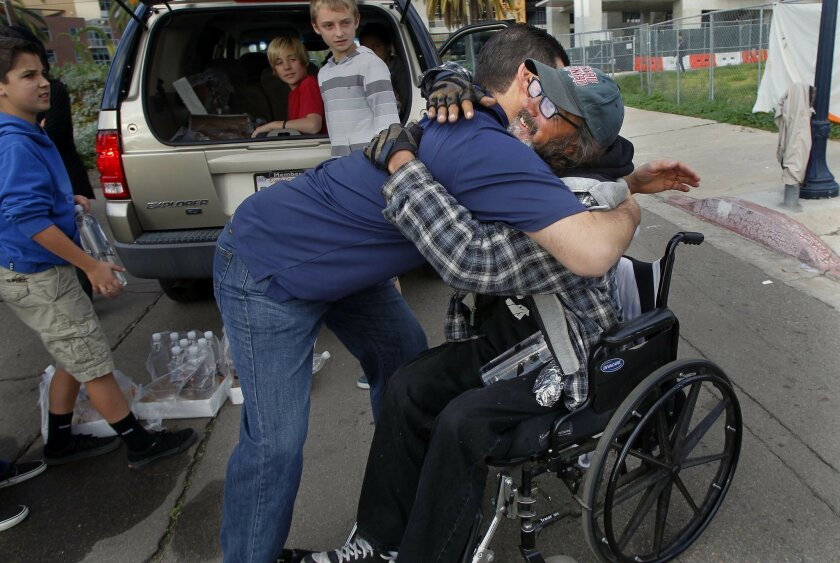 Michael Johnson (left) gets a big hug from friend David McCormick during a breakfast-delivery run near Petco Park. Last summer, Johnson and his wife took McCormick to Coronado to watch their son and his friends play in a beach soccer tournament.