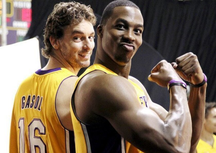 Dwight Howard flexes as he and Pau Gasol wait to take photographs during media day.