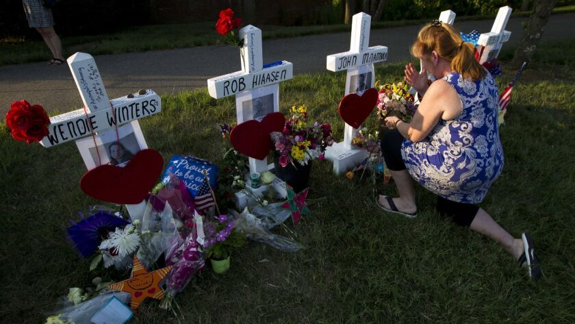Colleen Joseph prays over the crosses at a makeshift memorial at the scene outside the office buildi