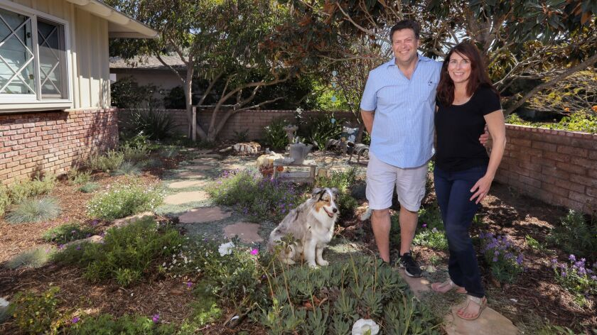 Ken Klestinec and Nina Ronstadt with their dog, Cleo, in their new drought-tolerant front yard.