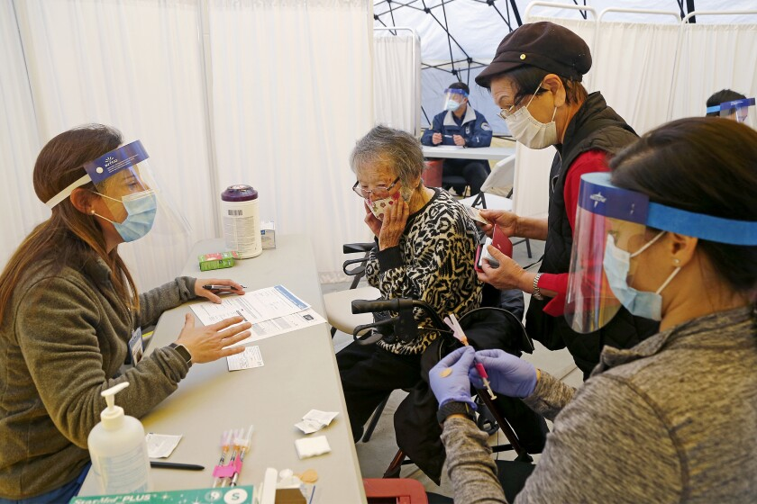 A nurse prepares to administer a COVID-19 vaccine to a woman in Huntington Beach.