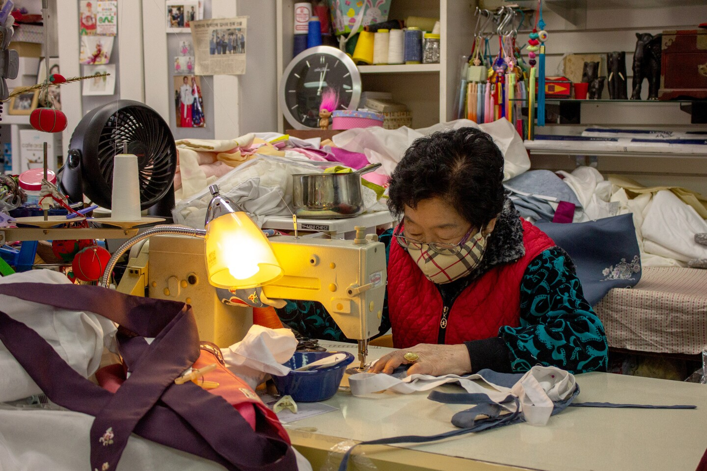 The store owner alters hanbok, traditional Korean clothing worn for celebrations, in her shop which is one a few in Orange County.