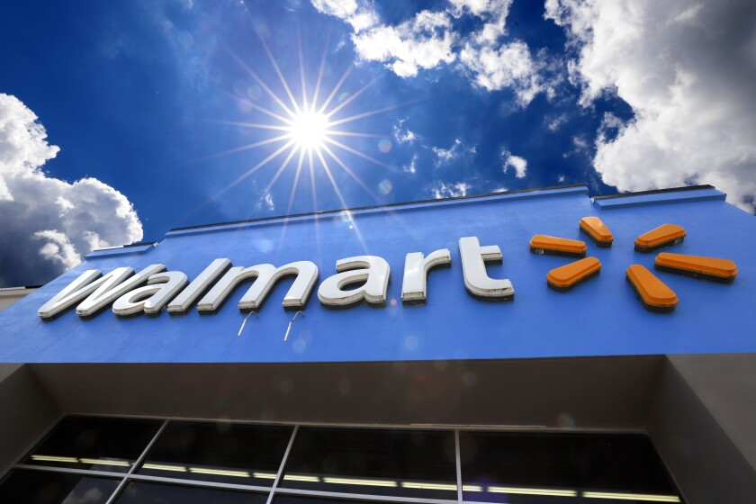 FILE - This June 25, 2019, file photo shows the entrance to a Walmart in Pittsburgh. Walmart and Tesla have settled a lawsuit filed by the retail giant alleging that Tesla installed rooftop solar panels that caught fire. The companies say in a joint statement issued Wednesday, Nov. 6, that both sides have resolved issues raised by Walmart in the case. (AP Photo/Gene J. Puskar, File)