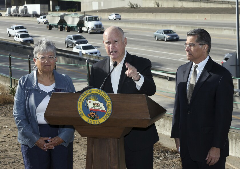 Then-Gov. Jerry Brown, center, blasts a Trump administration plan to roll back vehicle emissions standards in 2018. Brown is flanked by California Air Resources Board Chair Mary Nichols and Atty. Gen. Xavier Becerra.