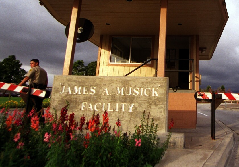 A guard stands at the front gate of the James A. Musick Facility in Irvine.