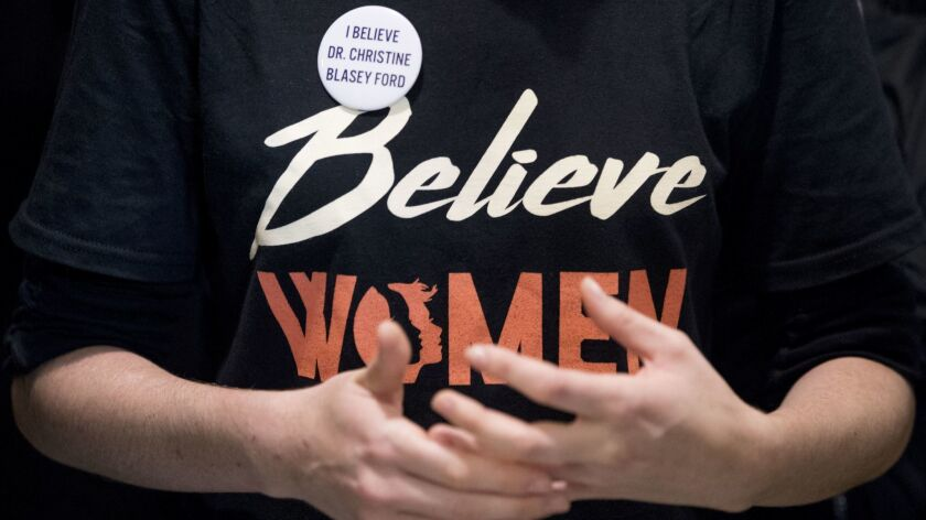 "A woman wears a shirt that reads ""Believe Women"" with a button that reads ""I Believe Dr. Christine B"