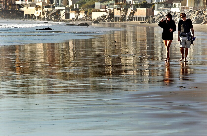 Nadine Froger, left, and Jean Jacques Pochet walk along Broad Beach in Malibu.