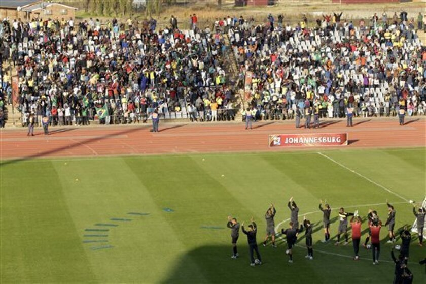 Brazilian national soccer players wave to fans attending a training session in Johannesburg, South Africa, Thursday, June 3, 2010. Brazilian team is preparing for the upcoming soccer World Cup, where they will play in Group G. (AP Photo/Andre Penner)