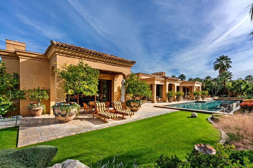 The Mediterranean mansion expands to a lush backyard with water, mountain and golf course views.