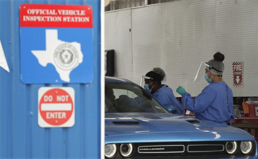Unas personas administran pruebas de COVID-19 en un centro de inspección, en San Antonio, Texas