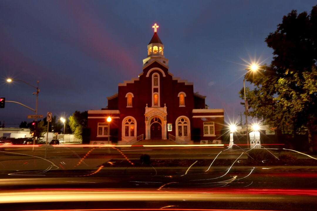 A church building at night with streaks from car lights in the foreground