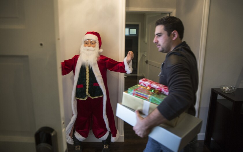 Peter Rabadi carries Christmas gifts out of his home in Porter Ranch. Peter and his wife, Danielle, will be staying with relatives until the leak from a nearby Soutthern California Gas Co. well is fixed.