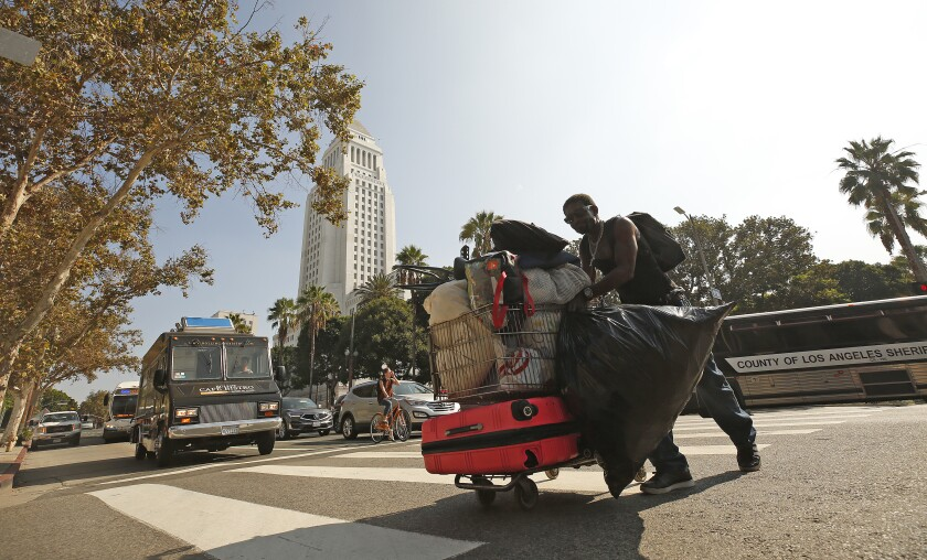 A man moves his belongings back to the sidewalk on 1st Street in downtown Los Angeles after a cleanup in October.