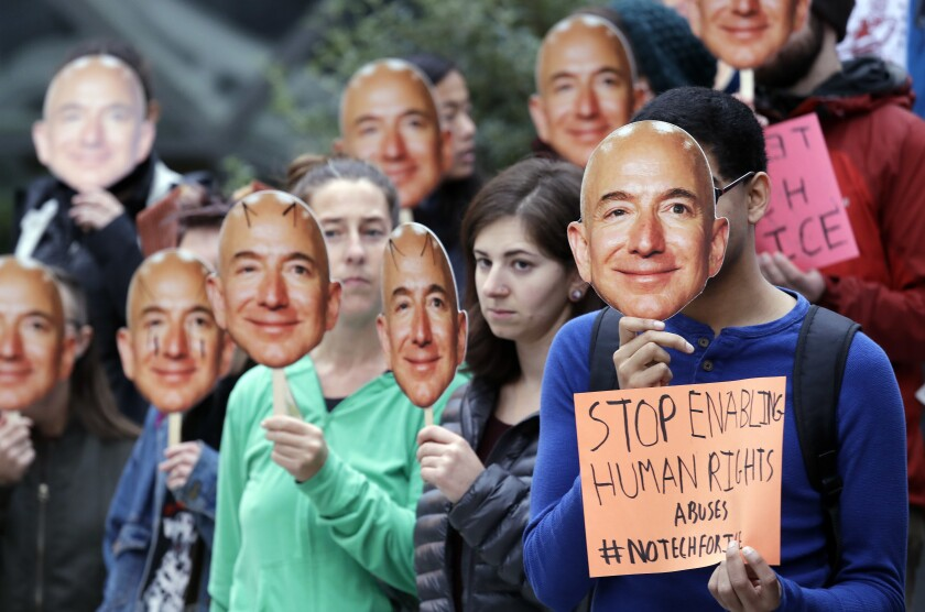 Demonstrators hold images of Amazon CEO Jeff Bezos over their faces.