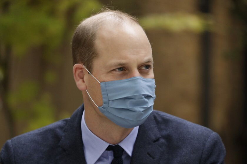 A man wearing a suit and a gray mask over his nose and mouth