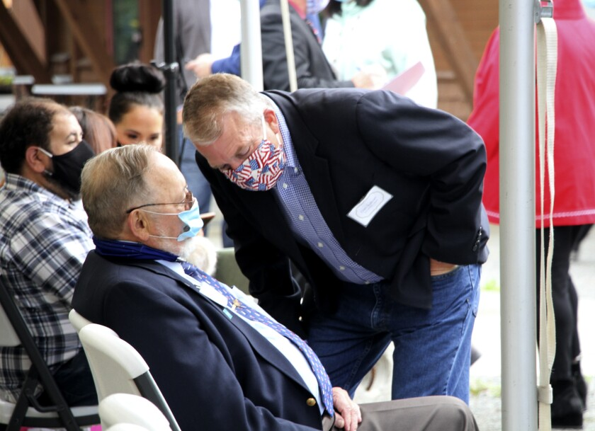 A masked U.S. Sen. Daniel Sullivan leans down to speak to a seated U.S. Rep. Don Young, also masked.